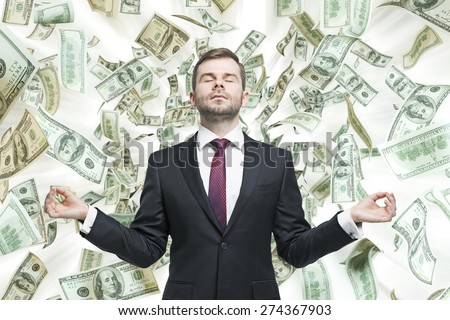 Meditative young businessman. Dollars notes are falling down from the ceiling. A concept of career success. - stock photo