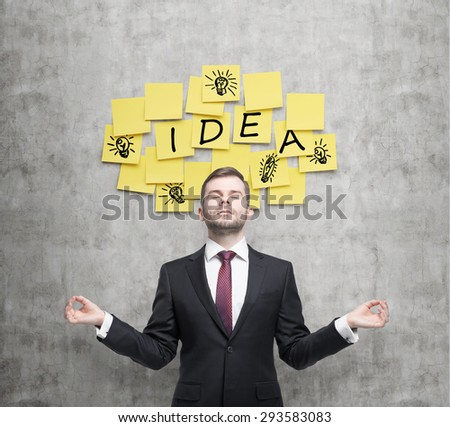 Meditative young businessman is looking for new business ideas. Yellow stickers with the word ' idea' and sketches of ' light bulbs ' are hanged on the concrete wall. - stock photo