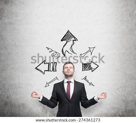 Meditative young businessman is trying to find the best solution for business development. Arrows on the concrete wall. - stock photo