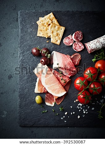 Mediterranean antipasto on a black slate  - stock photo