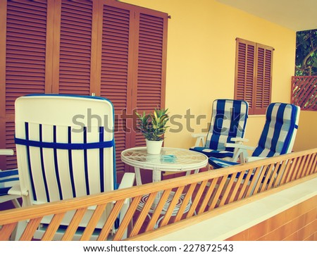Mediterranean apartment terrace exterior with chairs. Vintage effect. - stock photo