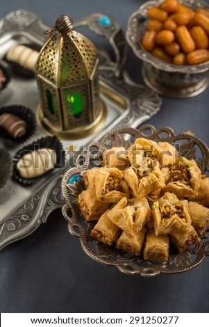 Mediterranean baklava, date-chocolates, balah and Ramadan lamp. A festive food. - stock photo