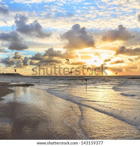 Mediterranean beach sunset view and kite surfing - stock photo