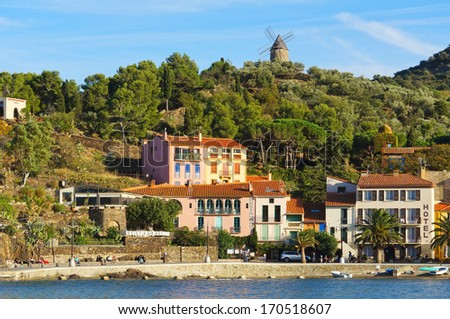 Mediterranean coast in Collioure village with hotel restaurant and a windmill at the top of the hill, Roussillon, Vermilion coast, Pyrenees Orientales, France - stock photo