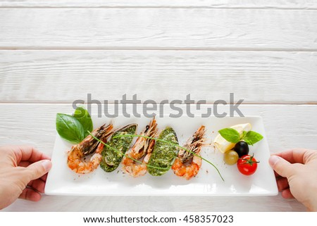 Mediterranean exotic seafood serving, copyspace. Hands put plate with cooked shrimp and mussels on white wooden background - stock photo