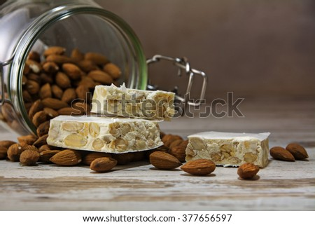 mediterranean festive torrone or nougat in front of a glass jar with almonds on a rustic wooden table, copy space, close up with selected focus and very narrow depth of field - stock photo
