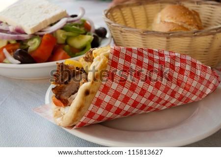 Mediterranean gyros pita and greek salad. A greek gyros typically include tomato, onion, fried potatoes tzatziki in addition to the meat. Taken in Kos, Greece - stock photo