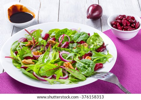 Mediterranean healthy red beans salad with mix of lettuce leaves and walnuts on a white dish on a wooden table, close-up - stock photo