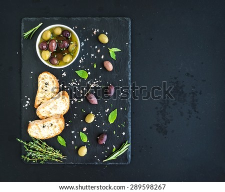 Mediterranean olives with herbs and ciabatta slices on black slate tray over dark grunge background, top view, copy space - stock photo