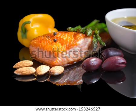 Mediterranean omega-3 diet. Fish steak, olives, nuts and herbs isolated on black background with reflection. - stock photo