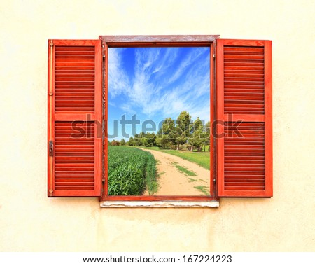 Mediterranean open window with shutters and rural curved road along a green wheat field - stock photo