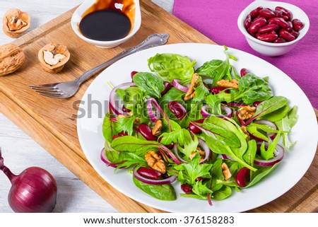 Mediterranean red beans salad with mix of lettuce leaves and walnuts on a white dish on a cutting board, on the old wooden table, close-up, top view - stock photo