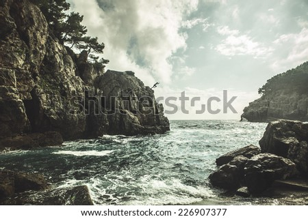 Mediterranean rocky shores and landscape - Odysseus cave on island Mljet near Dubrovnik, tourist attraction, Croatia. Young man jumping from the cliff in distance. Cliff jumping recreation on seaside - stock photo
