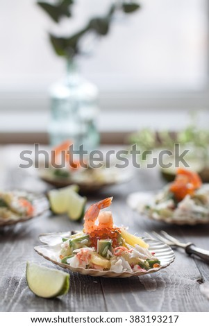 Mediterranean salad with king crab, shrimps, avocado, pineapple and caviar in a natural shell - stock photo