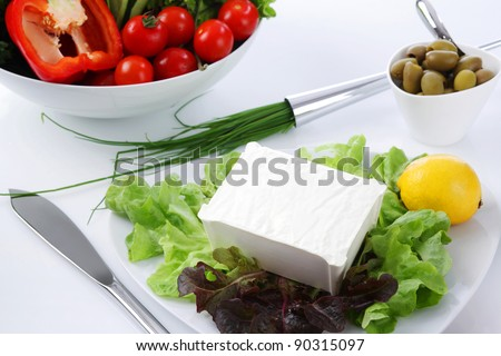 Mediterranean salad with tomatoes, olives, cheese and a lemon, served at a restaurant - stock photo