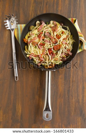 Mediterranean salami spaghetti freshly cooked in a fry pan ready to serve. - stock photo