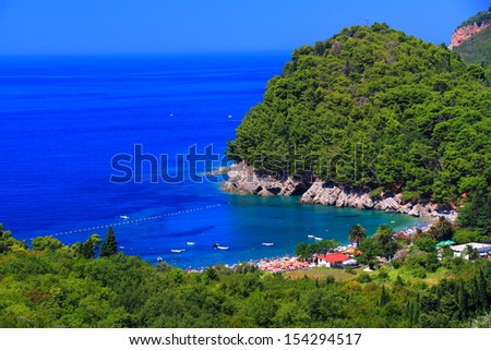Mediterranean vegetation surrounds a small beach, with the Adriatic sea in the background - stock photo
