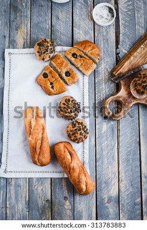 Mediterranean whole wheat bread concept. Include variety wheat bread focaccia with olives, baguette sandwich, sunflowers seeds buns from above on linen napkin over on blue shabby chick wooden table. - stock photo