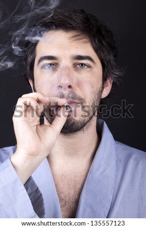 Medium closeup of an adult man (30 years old), which  appears to be quite a bum, numbingly gazing forward, concentrated in smoking a marijuana spliff (aka reefer; joint). Dark gray background. - stock photo