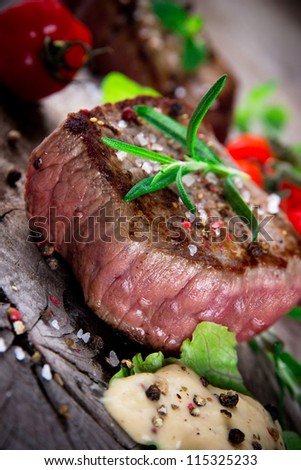 Medium grilled bbq steak with fresh herbs and tomatoes - stock photo