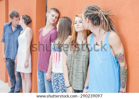 Medium group of young people kissing and standing in row near red wall background. They celebrate a holiday of International, World Kissing Day 6 July or Valentine's Day - stock photo