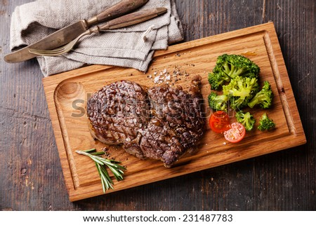 Medium rare grilled Beef steak Ribeye with broccoli on cutting board on wooden background - stock photo