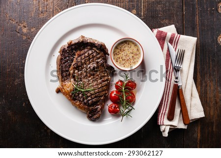 Medium rare grilled Beef steak Ribeye with grilled cherry tomatoes and Pepper sauce on white plate on wooden background - stock photo