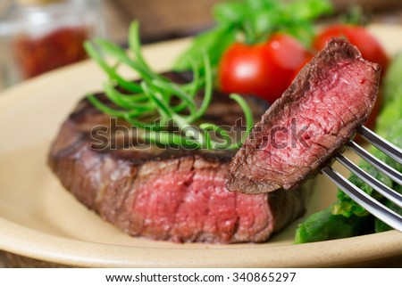 medium roasted steak with asparagus and tomatoes on plate - stock photo