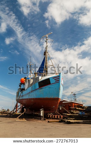 Medium-sized fishing boat standing in a drydock for repairs. - stock photo