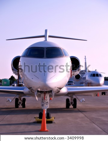 Medium sized jet planes sit on the tarmac at a small airport - stock photo
