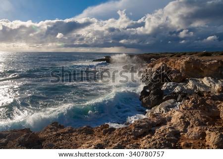 medium waves crashing on the rocks, blue sky with clouds  - stock photo
