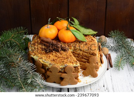 Medovik or layered honey cake decorated with gingerbread man cookies, tangerines, spices and pine tree branches for Christmas dinner - stock photo