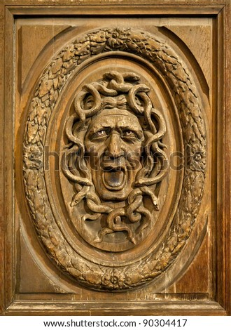 Medusa head carved on a wooden door - stock photo
