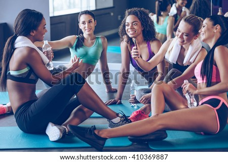 Meet up on the mat. Beautiful young women in sportswear discussing something with smile and using smartphone while sitting on exercise mat at gym - stock photo