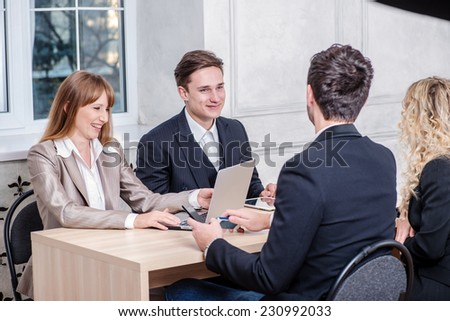 Meeting colleagues. Two businessmen in a meeting while four successful businessman sitting at the table at the meeting and discuss business. Businessmen wearing formal clothes - stock photo