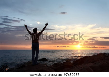 Meeting dawn on  sea.  silhouette of  man. - stock photo