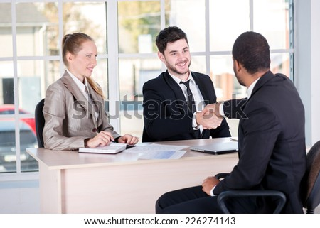 Meeting of partners. Three successful business people sitting in the office and do business while businessmen shake hands with each other and work at a laptop - stock photo