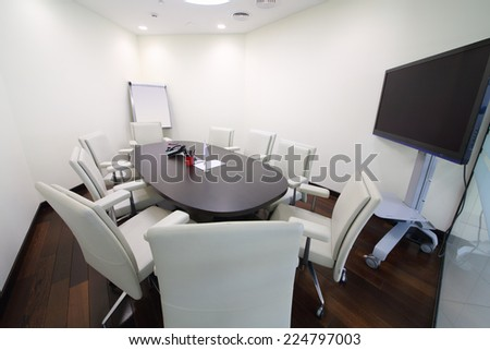 Meeting room with a round table and white chairs  - stock photo