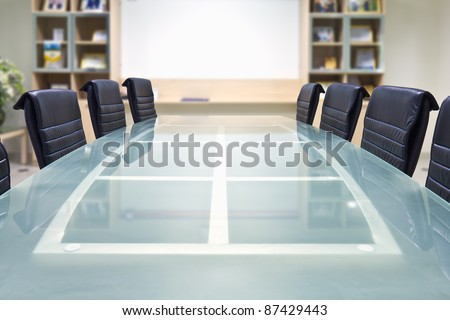 Meeting room with glass top table and armchairs, office interior - stock photo