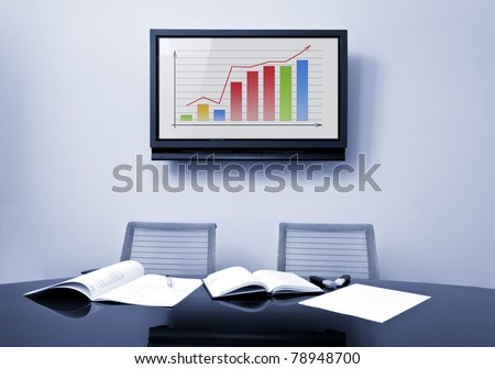 Meeting table at office in front of a huge plasma TV screen - stock photo