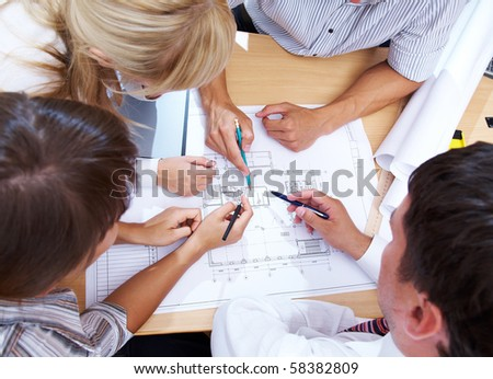 Meeting the team of engineers working on construction project at the table.  Up view - stock photo