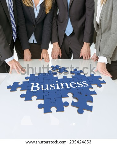Meeting with people around a table with a puzzle with the word business - stock photo