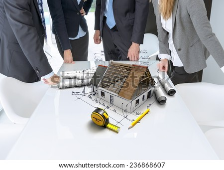 Meeting with people around a table with a residential architectural model with technical notes and details, blueprints and a tape measure - stock photo