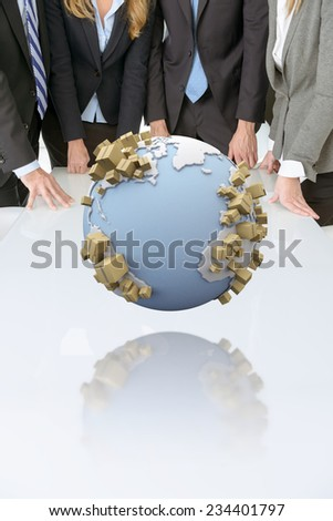 Meeting with people around a table with a world surrounded by cardboard boxes - stock photo