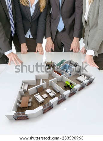 Meeting with people around a table with an architecture model showing an apartment - stock photo