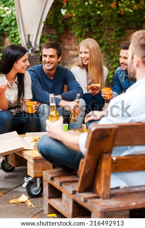 Meeting with the best friends. Group of joyful young people talking to each other and eating pizza while sitting outdoors - stock photo