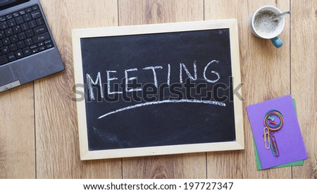 Meeting written on a chalkboard at the office - stock photo
