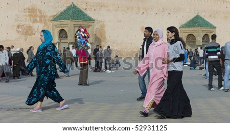 MEKNES - APRIL 18: Arabic women walking on square near he city wall in Meknes in the afternoon April 18, 2010 in Meknes, Morocco. - stock photo