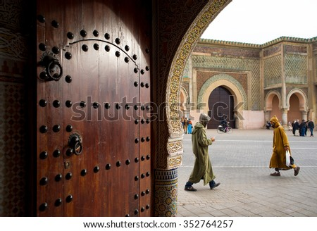 Meknes, Morocco - December 9, 2015:  People with djellaba walking front of Bab Mansour gate, view from inside a entry hall of a classical building. Bab Mansour gate is the largest in North Africa. - stock photo