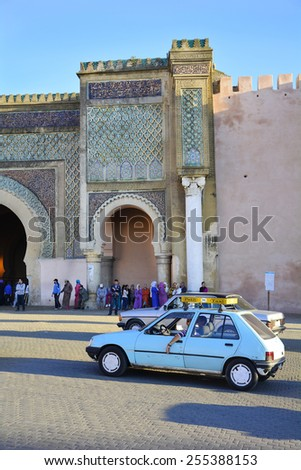 MEKNES, MOROCCO - NOVEMBER 19: Unidentified people and petit taxi in front of Bab el-Mansour, petit taxis are a preferred mode of transport up to 4 persons, on November 19, 2014 in Meknes, Morocco - stock photo